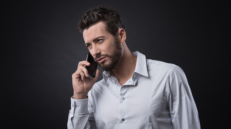 beau jeune homme: Young attractive businessman having a phone call with his smartphone Banque d'images