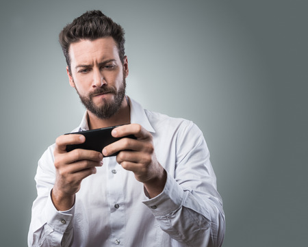 Handsome young man playing with his smartphone