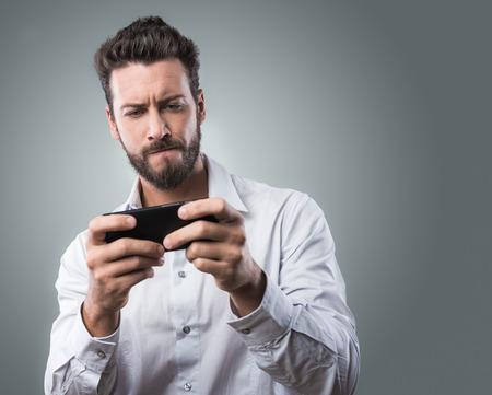 jeu: Beau jeune homme jouant avec son smartphone