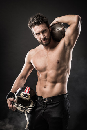 boy  naked: Attractive shirtless football player holding protective helmet and posing
