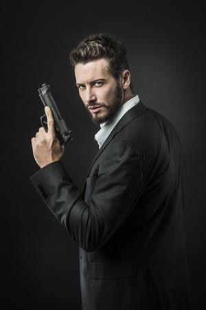 Zelfverzekerd undercover agent met een pistool tegen een donkere achtergrond Stockfoto