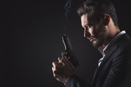 Brave cool man holding a gun on dark background 스톡 콘텐츠