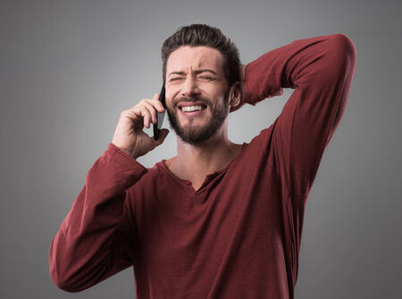 bad news: Young handsome man having a phone call and receiving bad news Stock Photo
