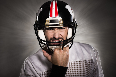 Aggressive football player with protective helmet posing