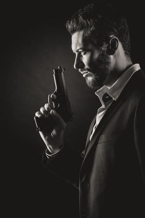 Brave cool man holding a gun on dark background Reklamní fotografie