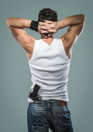 undershirt: Handsome masculine criminal with hands up behind head rear view