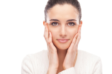 Belle modèle féminin toucher son lisser une peau éclatante de visage et de sourire à la caméra Banque d'images