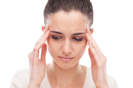 frontal: Beautiful young woman with headache touching her temples Stock Photo
