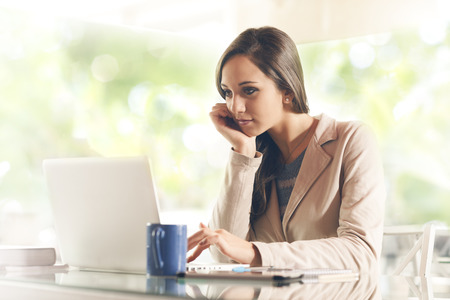 Busy young business woman working at desk typing on a laptop Stockfoto