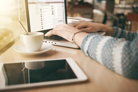 typing: Mujer que usa un ordenador port�til durante una pausa para el caf�, las manos de cerca