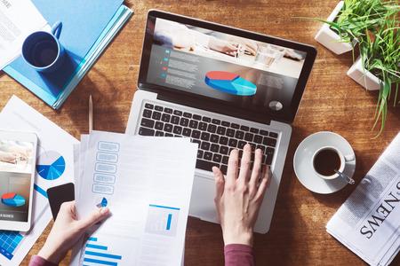 grafica de pastel: Informe financiero con gráfico circular y datos en un ordenador portátil con las manos de la mujer de negocios en el trabajo Foto de archivo
