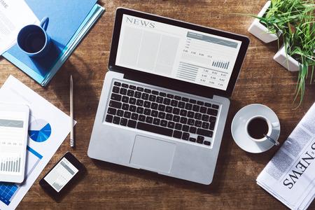 reporte: Noticias de negocios financieros en l�nea en un ordenador port�til con caf� y papeler�a