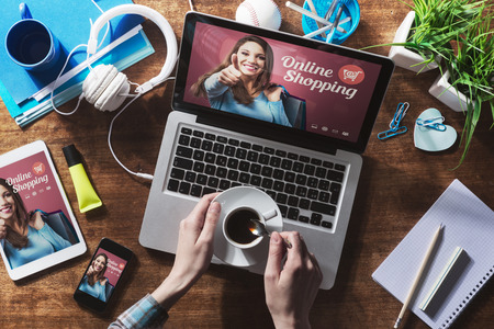 Online shopping website on laptop screen with female hands holding a coffee