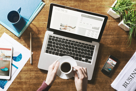 Financial business news online on a laptop with coffee and stationery Foto de archivo