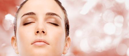 Belle femme montrant son éclatante peau du visage lisse et posant Banque d'images