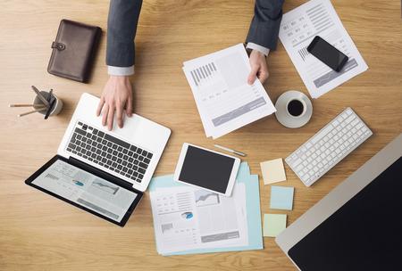 psací stůl: Obchodník pracující v kanceláři a kontrole finanční zprávy s počítači a papírování kolem, pohled shora