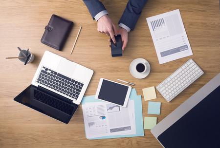 trabajador oficina: Empresario de trabajo en la oficina escritorio manos vista superior con informes port�tiles y financieros: �l est� usando un tel�fono inteligente de pantalla t�ctil m�vil