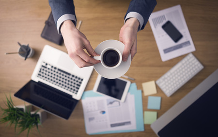 businessman working at his computer: Professional businessman having a coffee break while working at his office desk, hands close-up top view with computer and paperwork on background