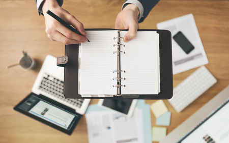 Businessman working at office desk and writing down notes on his agenda, laptop and financial report on background, top view. photo