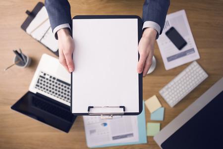 Homme d'affaires travaillant au bureau et montrant un presse-papiers avec un document vierge, des ordinateurs et de la papeterie sur fond, vue de dessus