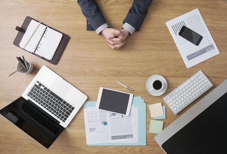 Confident businessman assis à son bureau, les mains jointes, les documents et les ordinateurs autour, les mains détail vue de dessus