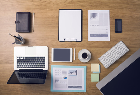 Businessmans tidy desktop and work tools with paperwork, computer, touch screen devices and stationery on a wooden surface, top view photo