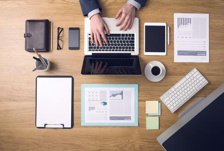ejecutivo en oficina: Empresario de trabajo en un ordenador port�til en el escritorio de oficina con el papeleo y otros objetos a su alrededor, la vista superior Foto de archivo