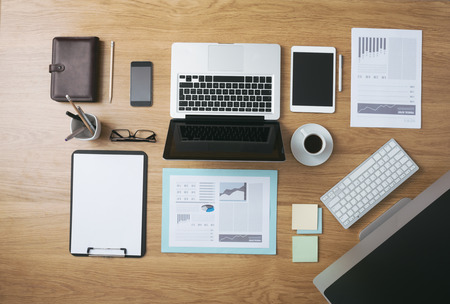 desk tidy: Businessmans tidy desktop and work tools with paperwork, computer, touch screen devices and stationery on a wooden surface, top view Stock Photo