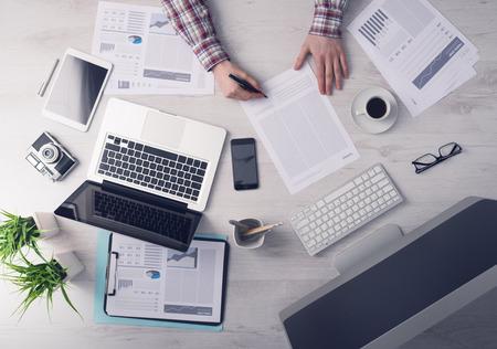 signing: Imprenditore di lavoro alla scrivania in ufficio e di firmare un documento, computer e documenti tutto intorno, vista dall'alto Archivio Fotografico