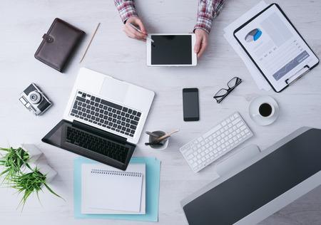 tecnologia: Empresário de trabalho na mesa de escritório e usando um tablet digital, computador, laptop e vários objetos ao redor, vista de cima