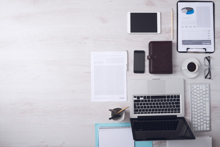 Businessman tidy desktop with laptop, tablet, smartphone, financial reports and various objects, copyspace on the left, top view