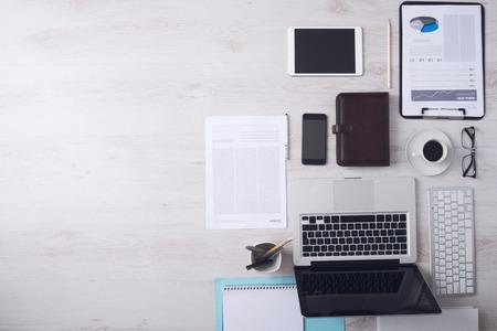 Zakenman opgeruimd bureaublad met laptop, tablet, smartphone, financiële rapportages en diverse voorwerpen, copyspace aan de linkerkant, bovenaanzicht