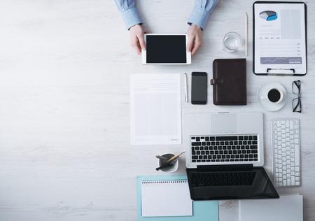 personas trabajando en oficina: El hombre de negocios que trabajan en escritorio de oficina y el uso de un control digital de pantalla tablet manos detalle, equipo y objetos a la derecha, vista desde arriba