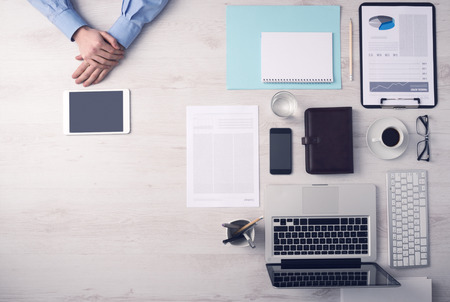 occupations and work: Imprenditore di lavoro alla scrivania in ufficio e con un touch screen digitale mani tablet dettaglio, computer e oggetti a destra, vista dall'alto