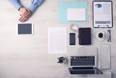 Obchodník pracující v kanceláři a pomocí digitální dotykové obrazovce tabletu ruce detail, počítač a objekty na pravé straně, pohled shora