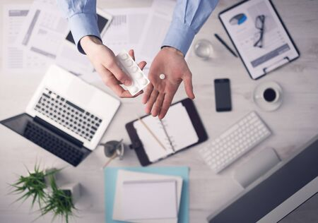 empleado de oficina: Oficinista que tomar una p�ldora y la celebraci�n de una ampolla manos de cerca con el escritorio en el fondo, vista desde arriba