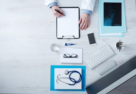 Professional doctor writing medical records on a clipboard with computer and medical equipment all around, desktop top view with copyspace Stockfoto
