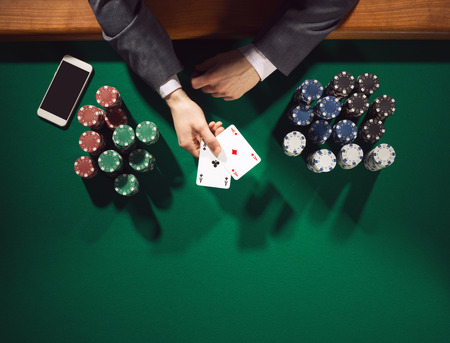 Elegant male poker player with smartphone holding two aces with stacks of chips all around, hands detail top view photo