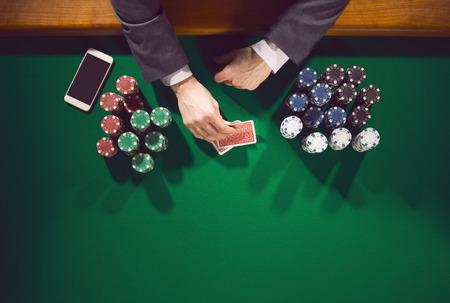 Elegante mannelijke pokerspeler met smartphone kijken naar zijn kaarten met stapels chips rondom Stockfoto