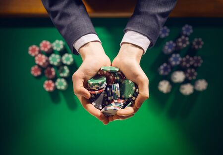 las vegas casino: Elegant male casino player holding a handful of chips with green table on background, hands close up top view Stock Photo