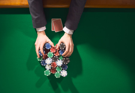 casino dealer: Poker player betting all in and holding a lot of chips stacks, hands close up, top view