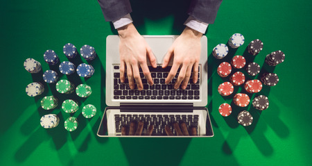online: Online players hands with laptop and stack of chips all around on green table top view, he is typing on the keyboard