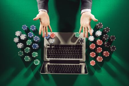 poker: Online players hands palms up with laptop and stack of chips all around on green table top view