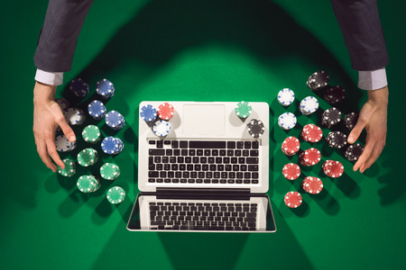 Online players hands with laptop on green table top view, he is winning and taking all chips photo