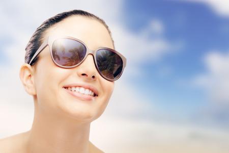Молодая женщина фотомодель улыбается и носить большие солнцезащитные очки, защиту от солнца и по уходу за кожей концепции
