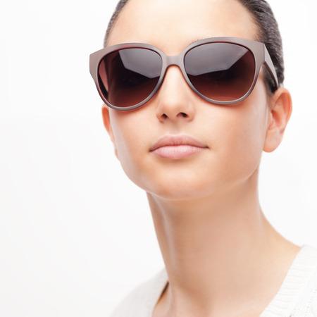 eyewear fashion: Young female fashion model wearing big sunglasses on white background Stock Photo