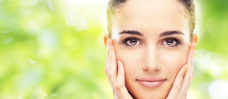 caras: Modelo de mujer hermosa que toca su suave piel radiante rostro y sonriendo a la cámara