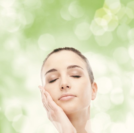 radiant: Beautiful young woman touching her radiant face skin with eyes closed on green background Stock Photo