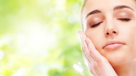 human skin: Joven y bella mujer tocar su piel radiante rostro con los ojos cerrados sobre fondo verde