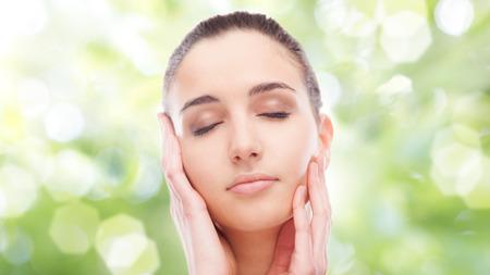 cosmeticos: Joven y bella mujer tocar su piel radiante rostro con los ojos cerrados sobre fondo verde